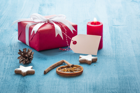 Christmas scenery with a red gift box, a lit candle, gingerbread cookies and cinnamon sticks on a blue wooden table
