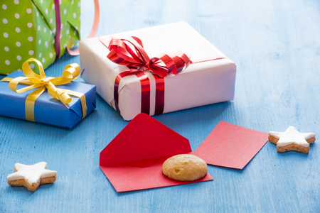 Opened envelope on a blue wooden table, surrounded by gingerbread stars shape cookies and gift boxes