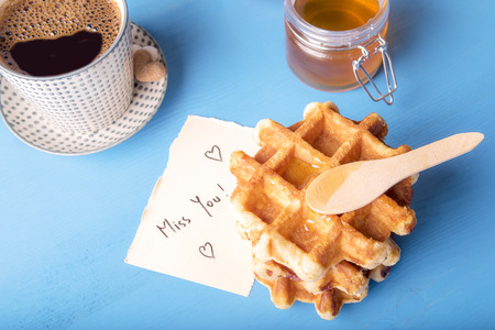 Tasty fresh waffles with honey on top, a cup of hot coffee and a cute note on a piece of paper with the miss you message and hearts, on a blue wooden table.