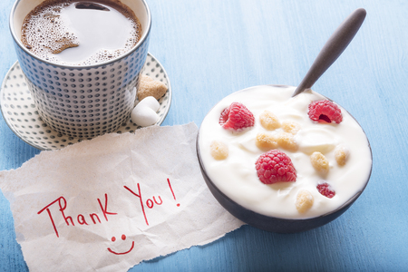 Bowl with yogurt, raspberry and cereal, a cup of hot coffee and a thank you note, with a smiley face, on a blue wooden table, in the morning light.
