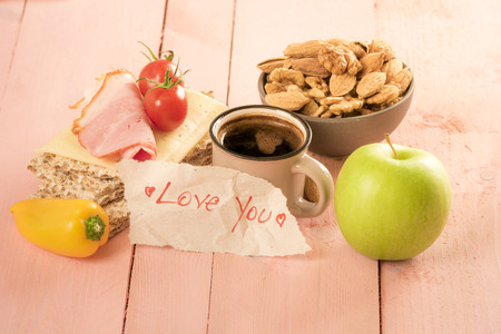 Romantic message wrote on a piece of paper near a cup of coffee and delicious breakfast, on a pink wooden table