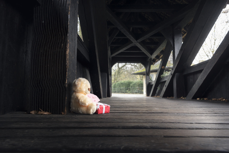 Gifting theme image with a stuffed bear toy holding a red gift box and a miss you note, sitting alone on an empty wooden bridge. Stock Photo