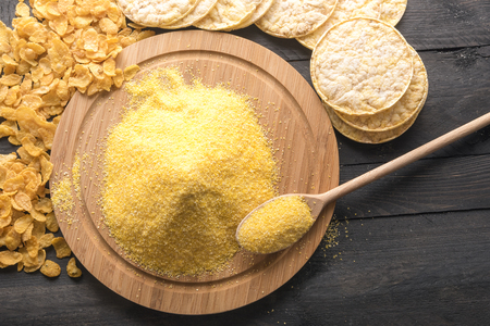 High angle view of a round wooden board full of corn flour, surrounded by products made of it, corn flakes and puffed corn cakes, on a black wooden table.