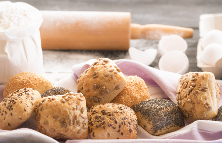 Close Up image with freshly baked buns, decorated with poppy seeds, sesame, flax and sunflower seeds, with flour, eggs and a rolling pin in the background. 版權商用圖片