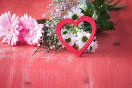 Love theme image with a red wooden heart propped against a bouquet of flowers, on a red wooden table. A concept for relationship, love, valentine day, greeting card.