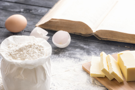 Baking theme image with a bag of wheat flour, butter and eggs, on a black wooden table, and an open book in the background.