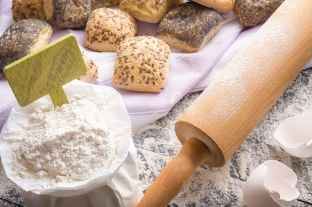 Food ingredients theme with a bag of flour with a blank wooden banner stick in it, a rolling pin and bread rolls baked from it, on a towel in the background. 版權商用圖片