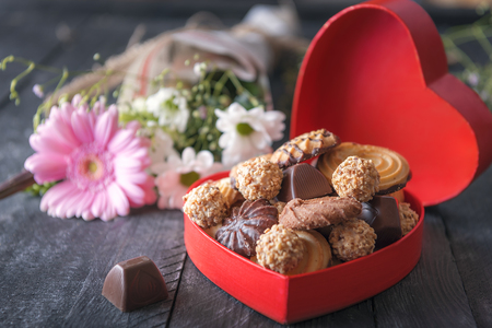 Valentine day theme image with a heart-shaped gift box full of cookies and chocolates, a lovely bouquet of flowers in the background, on a black table.
