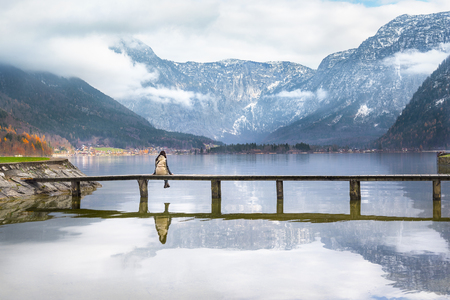Woman sitting on a wooden bridge over the lake Hallstatter, admiring the peaks of the Austrian Alps and their reflection in the water, in Hallstatt, Austria.