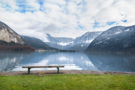 Holiday locations theme image with the Dachstein mountains reflected in the Hallstatter lake water and a wooden bench placed on its shore, in Hallstatt, Austria.