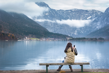 Woman sitting on a wooden bench, on the shores of the Hallstatter lake, using smartphone to photograph the Austrian Dachstein mountains, in Hallstatt, Austria. Stock Photo