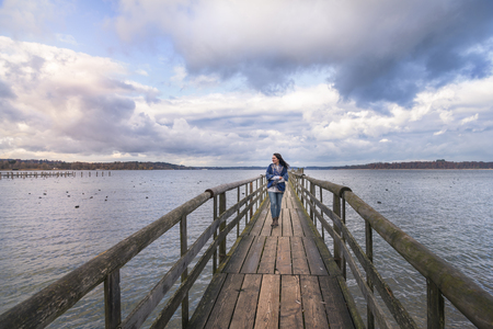 Beautiful young woman smiling and walking alone on a long wooden pontoon, over the lake Chiemsee, enjoying the fresh air and the sunset, in Germany.