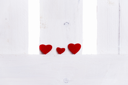 Family theme image with two big red hearts and a smaller one on the middle, on a white wooden fence. A concept for relationships, family, friends, feelings.