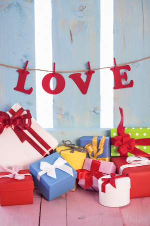 Numerous and colorful presents on a pink table and the word love tied to a linen string with wooden clips, on a blue fence, in the background. Stock Photo