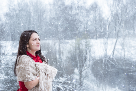 Attractive young woman with long dark hair, in a red dress, covered by a handmade shawl, smiling, looking up at the falling snowflakes.