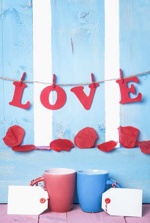 Red and blue cups with blank tags, the word love spelled from red paper letters tied to a string and soap rose petals, on a blue wooden fence