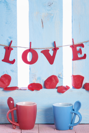 Red and blue mugs with spoons on their handle, the word love written with red paper letters, tied to a string and soap rose petals on a blue fence. Stock Photo