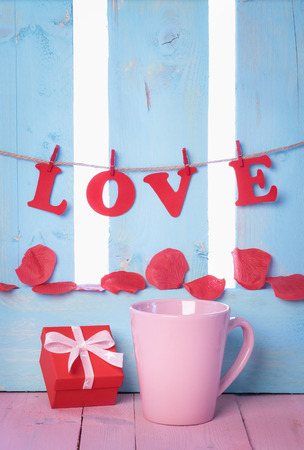 Red gift box near a pink cup with the word love spelled from red paper letters, tied to a string and soap rose petals on a blue wooden fence. 版權商用圖片