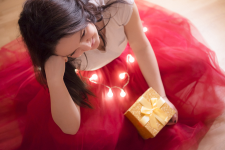 Beautiful young brunette woman, dressed in a red tutu, sitting on the floor, surrounded by Christmas lights and holding a gift box with a tied bow.