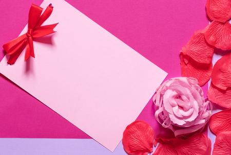 マゼンタの紙の背景に、石鹸のバラと花びらで囲まれた赤いネクタイの弓を持つピンクの紙のノート。誕生日やイベントのためのグリーティングカ