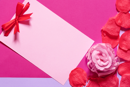 Pink paper note with a red tied bow surrounded by soap rose and petals, on a magenta paper background. Greeting card idea for birthdays and events.