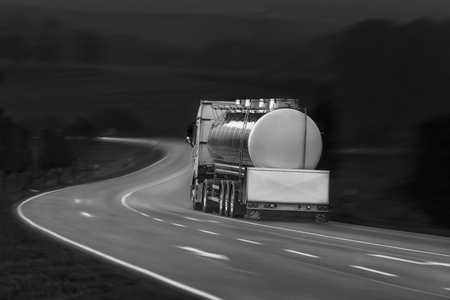 Black and white image with tanker truck driving on a countryside road, outside the german city Schwabisch Hall, Baden Wurttemberg, Germany