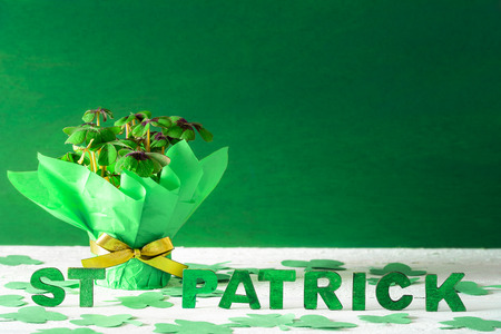 Clover pot wrapped in green paper and golden ribbon and bow and the words St Patrick written in green wooden letters, surrounded by paper shamrock.