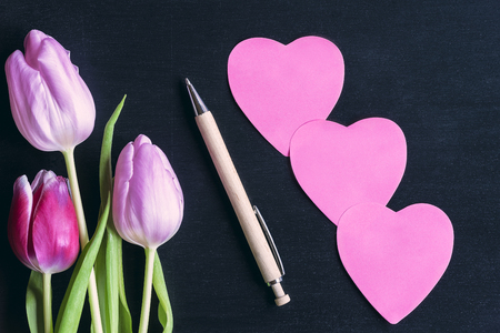 Colorful tulips, a wooden pen, and three pink heart shaped paper post-its, with space for messages, on a black wooden background. Stock Photo
