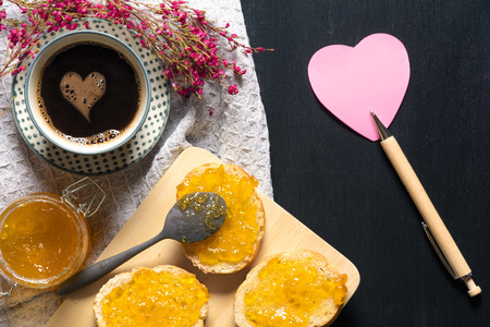 Romantic breakfast with flowers, heart shaped sticky note, bread with jam on a trencher and a cup of coffee with a foam heart, on a black table.
