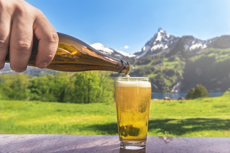 Hand of a man pouring beer from a bottle in a glass with a summer scenery in the background with mountains and green meadows, on a sunny day.