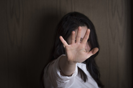 Brunette woman holding her hand stretched out toward the camera, covering her face, avoiding to be seen or stopping a problem.