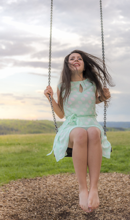 Beautiful brunette woman, dressed in a cute green dress, with bare foot, enjoying the swing on a playground at sunset.