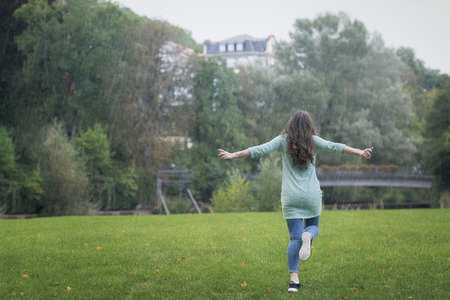 Brunette young woman, dressed casual, running happily in the rain with her arms wide spread, surrounded by green grass and trees, in Germany. Фото со стока