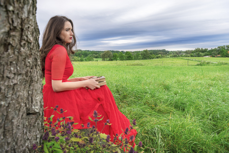 Beautiful woman, in an elegant red dress, sitting on a bench under a tree, with a book and pocket watch in her hands, in Schwabisch Hall, Germany. Stock Photo