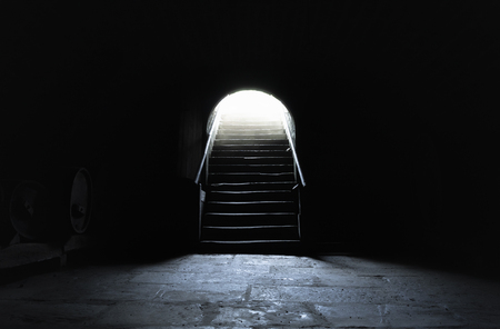 Medieval basement in complete darkness with a strong light at the exit Stock Photo