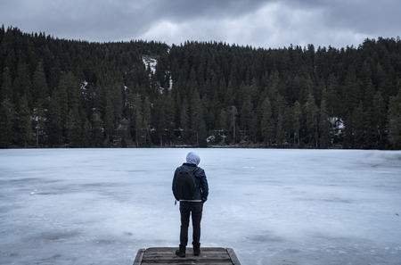Man standing on a wooden pier on the frozen lakeshore of Mummelsee lake, on a cloudy day of winter, in the Black Forest mountains, Germany.