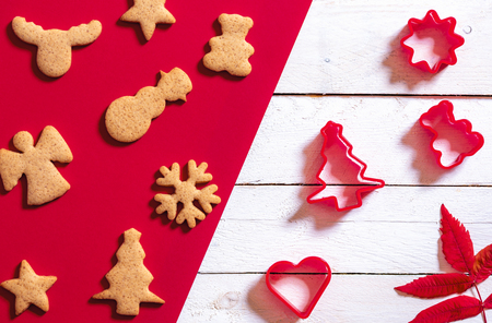 Red and white Christmas baking concept with ginger cookies in different Xmas shapes and cookie cutters. Minimalist Christmas context. Imagens