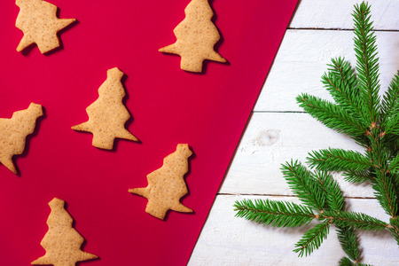 Minimalist Christmas image with ginger cookies in shape of an Xmas tree on a red background and a green fir twig on a white background.
