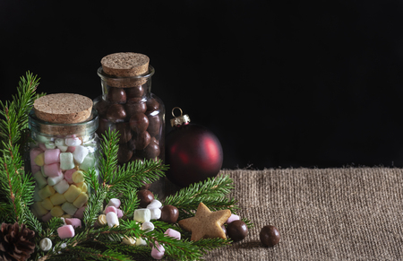 Christmas treats banner with bottles full of multi-colored mini marshmallows and chocolate candies, green fir twigs and Xmas ball, on jute fabric.