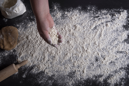 High angle view with a woman's hand spreading white flour over a black kitchen table