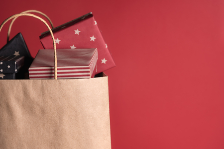 Shopping paper bag full of gifts wrapped in black and red paper, on a red background. 免版税图像