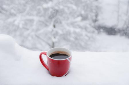 Tazza rossa con caffè arabo caldo posta su un balcone, in uno spesso strato di neve, con la natura innevata sullo sfondo, mentre nevica. Archivio Fotografico