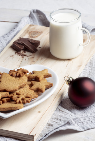 Close up with the traditional gingerbread cookies on a plate and a cup of milk on a wooden board on a kitchen towel