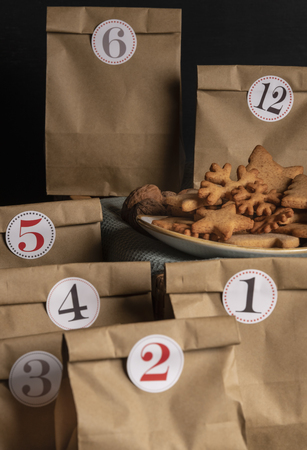 Paper bags with numbers on them and a plate with gingerbread cookies. Handmade advent calendar.
