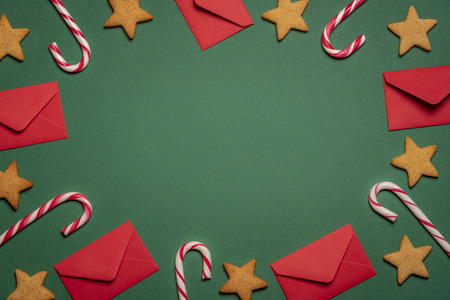 High angle view with sweet food like candy canes and gingerbread cookies together with small red envelopes on a green background