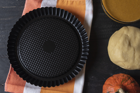 Above view of a black aluminum tray for baking sweets on a colorful kitchen towel and ingredients for pumpkin pie, the dough, and the filling. Stock Photo