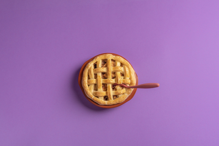 Top view of an apple pie in a rustic ceramic tray with a teaspoon in it, on a purple background. Ready to eat dessert. Flat lay. Minimalist style. 写真素材