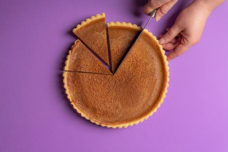 Mani di donna che affettano una torta di zucca su uno sfondo viola. Concetto culinario minimalista. Torta dolce fatta in casa. Dolce tradizionale delle feste. Vista dall'alto.