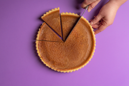 Woman hands slicing a pumpkin pie on a purple background. Minimalist culinary concept. Homemade sweet pie. Traditional holidays dessert. Top view. Stock Photo