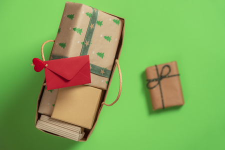 Paper bag full of Christmas gifts and a red envelope clipped on the handle and a separated gift on a green background. Gifting time context. Archivio Fotografico